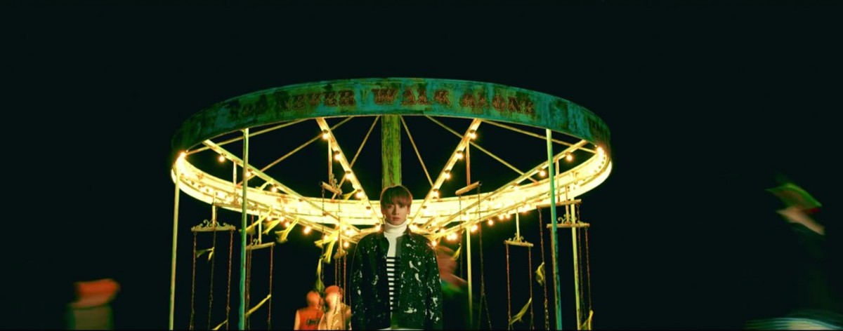 Jungkook in front of the carousel and the rest moving fast forward.
