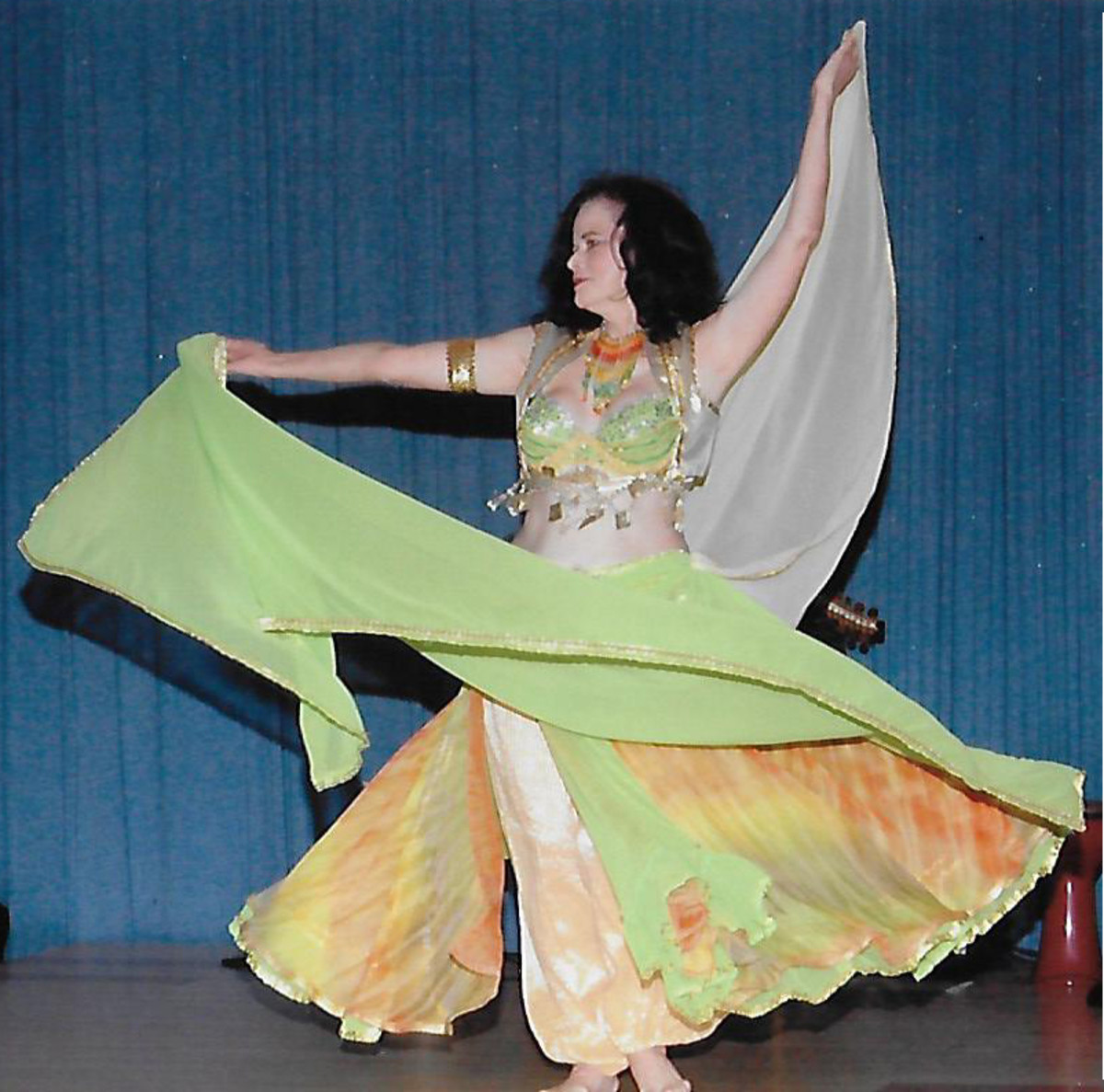 A belly dancer performing with 2 veils.
