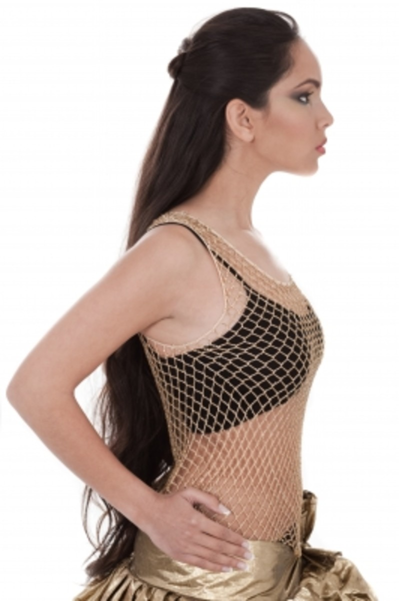 Side pose of a belly dancer with long black hair standing tall with confidence, self-esteem- and self-worth.