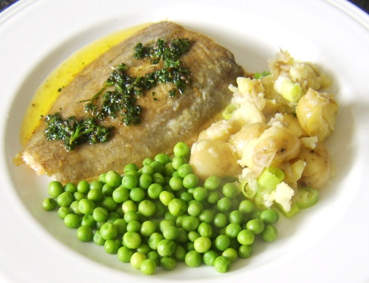 Lemon sole is plated with crushed potatoes and peas