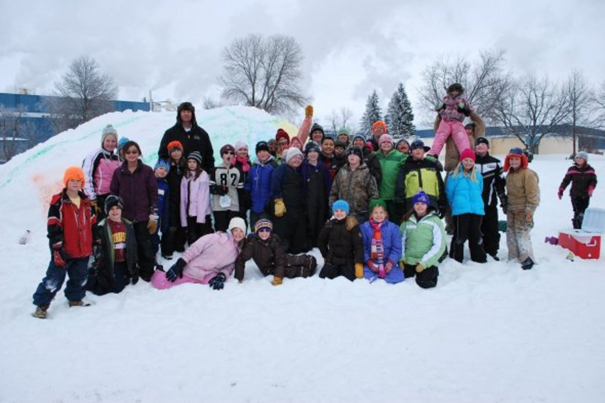 Kids pose after creating snow sculptures in Smokey Bear Park