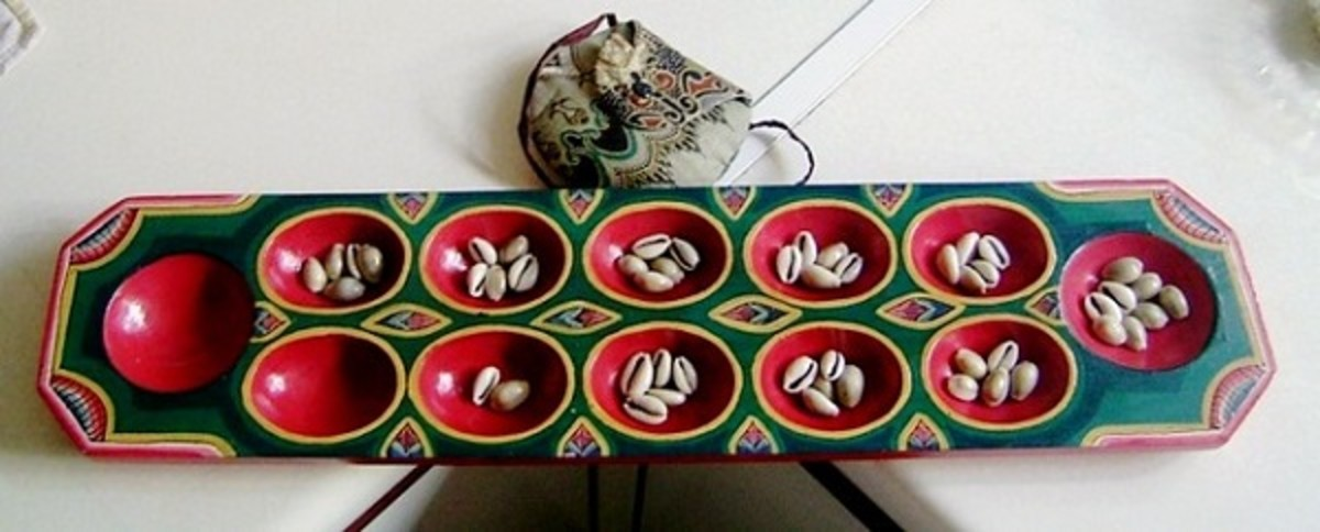 Beautiful mancala game board with cowrie shells as playing 'seeds'. Notice the delicate pouch that serves as storage for the cowrie shells.