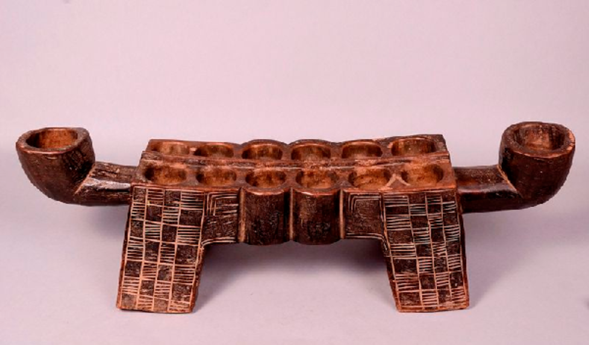 Traditional wood-carved mancala game with 2 rows of 6 holes each, and two seed store pits.
