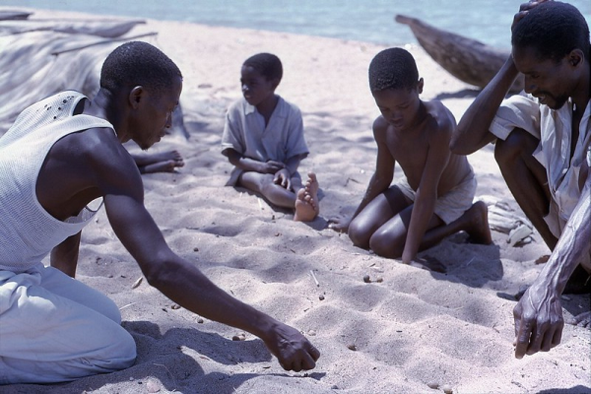 Young boys playing traditional mancala (bao) game with holes dug in the beach sand (Malawi 1966).