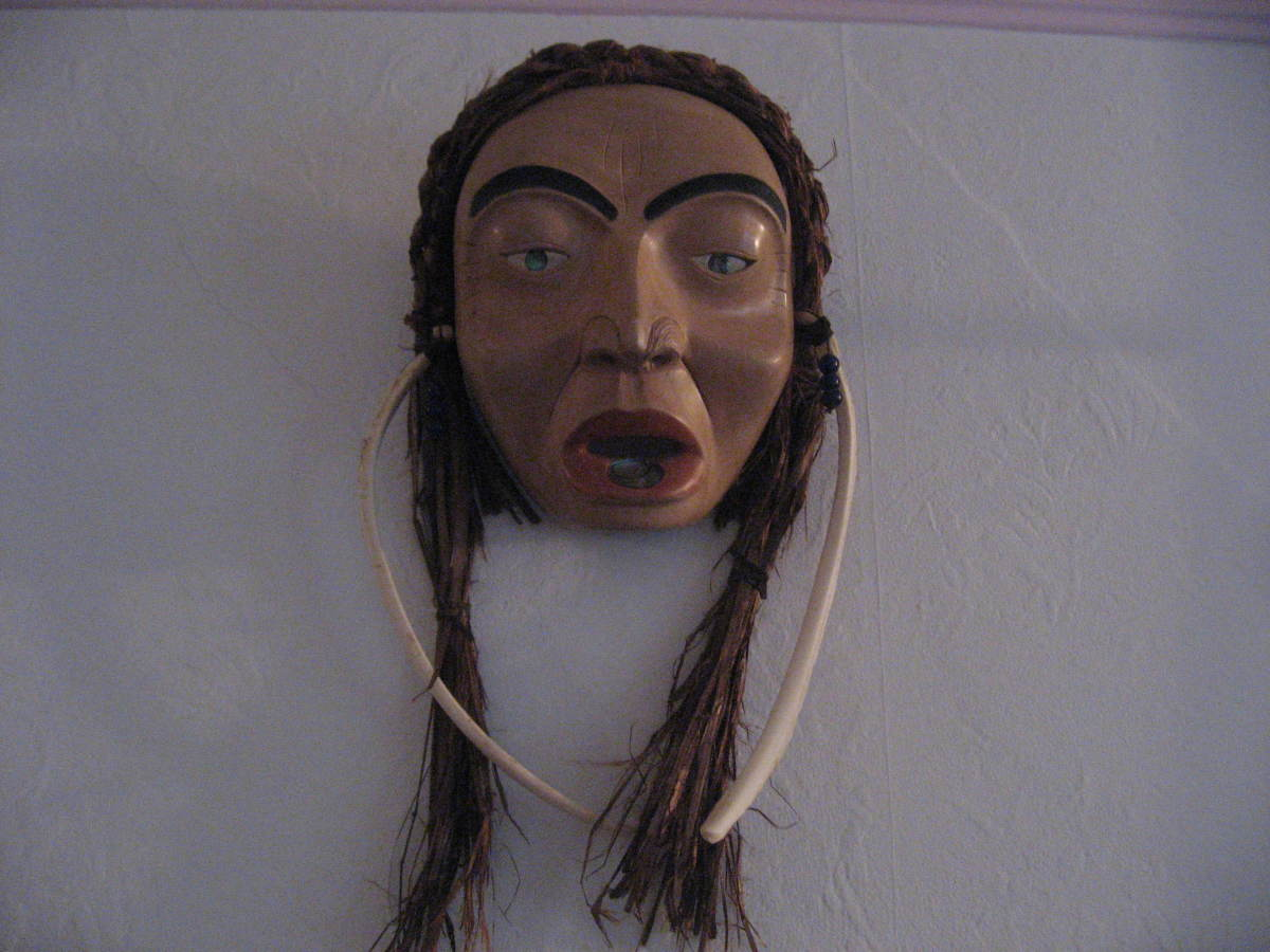Older woman with labret and bone earrings.This is carved in North West Coast style from Alder with cedar bark hair. it was carved by Marsha Ablowitz