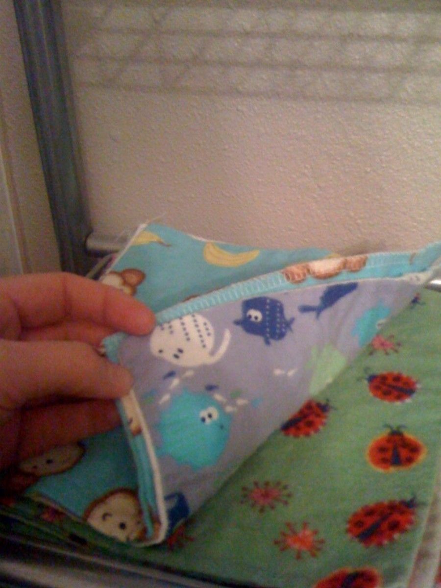 A stack of home made cloth baby wipes in a variety of colorful flannel fabrics.