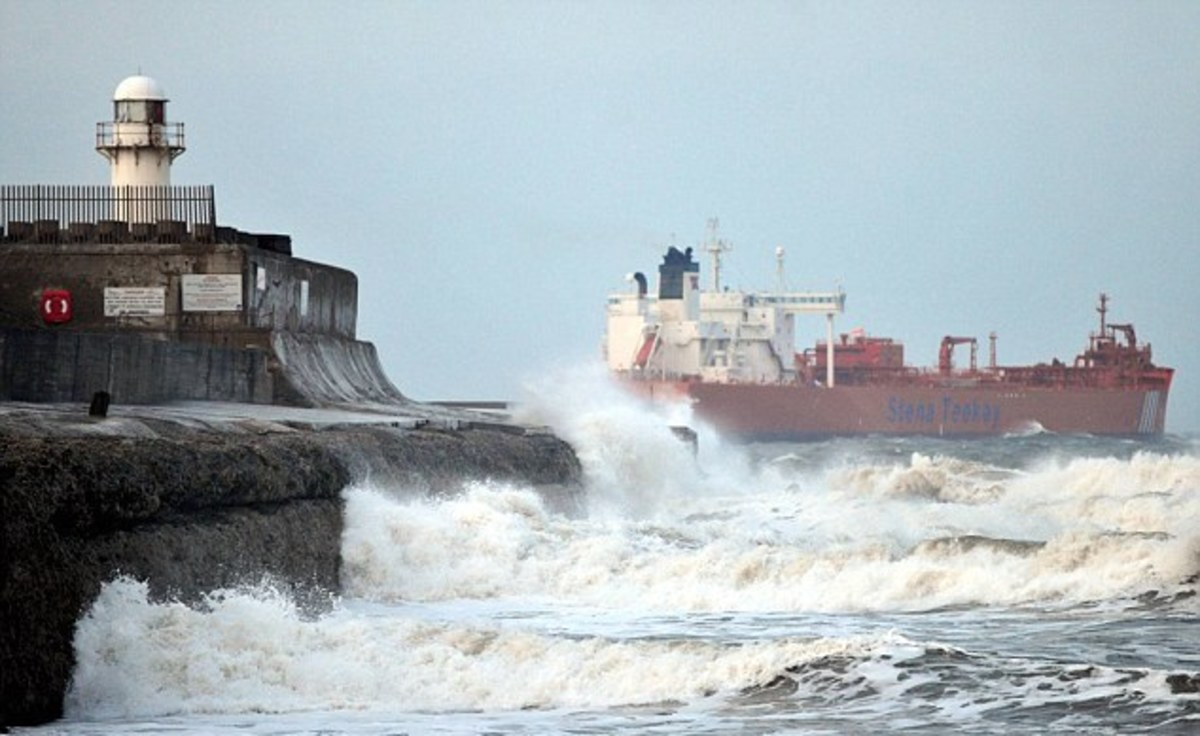 Looking past the South Gare beacon at a departing tanker - there is a steady flow of tankers and ore ships to Teesmouth, you'll see the pilot boats ploughing in and out  through the surf. The beacon tower''s been replaced, by a pair of masts