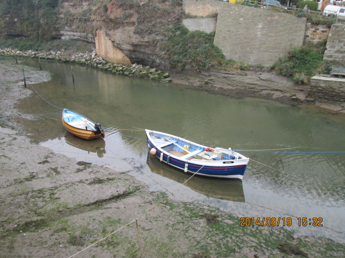 A Yorkshire coble and smaller craft at high tide on the creek, seen from the riverside walk near the small, narrow wooden footbridge