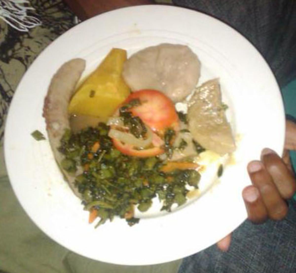A typical Jamaican-Rastafarian vegetarian food with Boiled Yam, Banana, Dumpling with tomato and callaloo