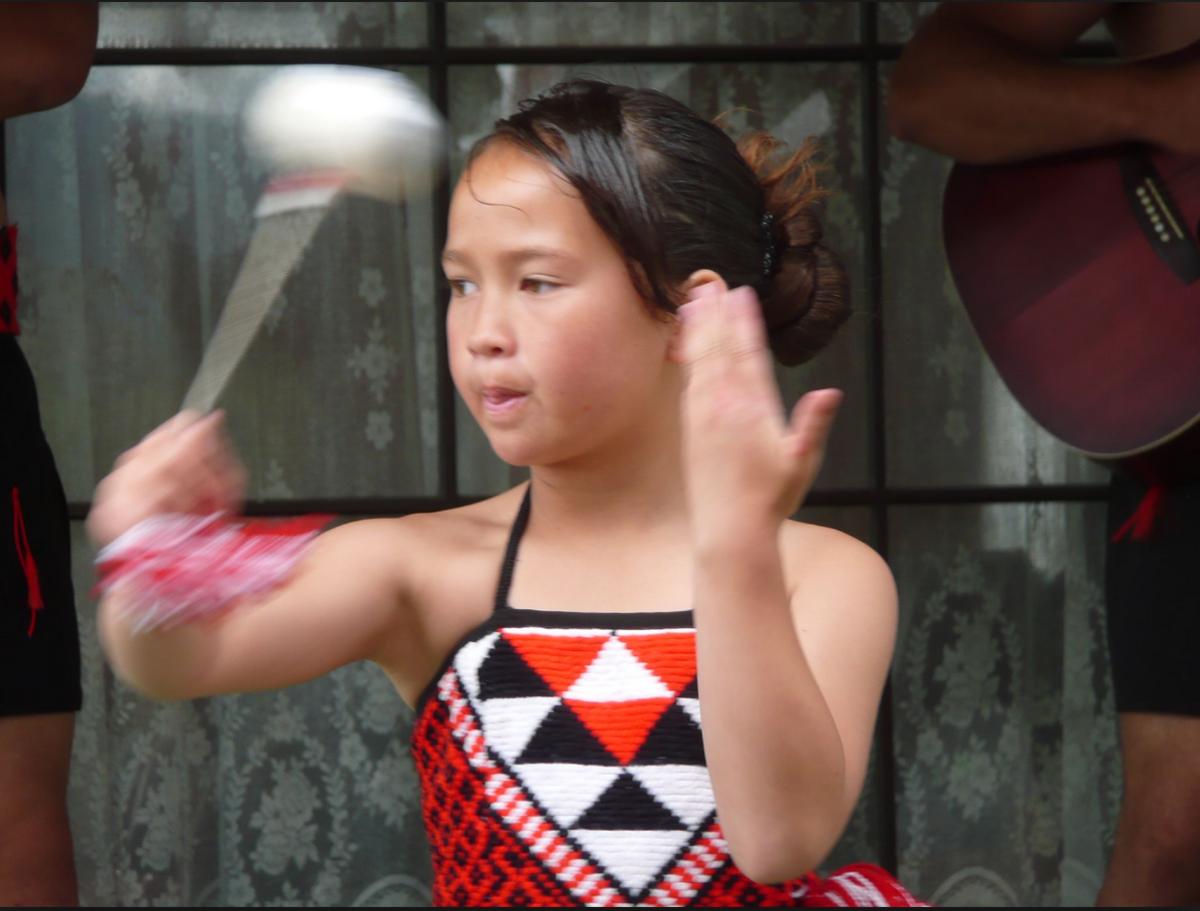 Young Maori girl in traditional dress dancing a poi.