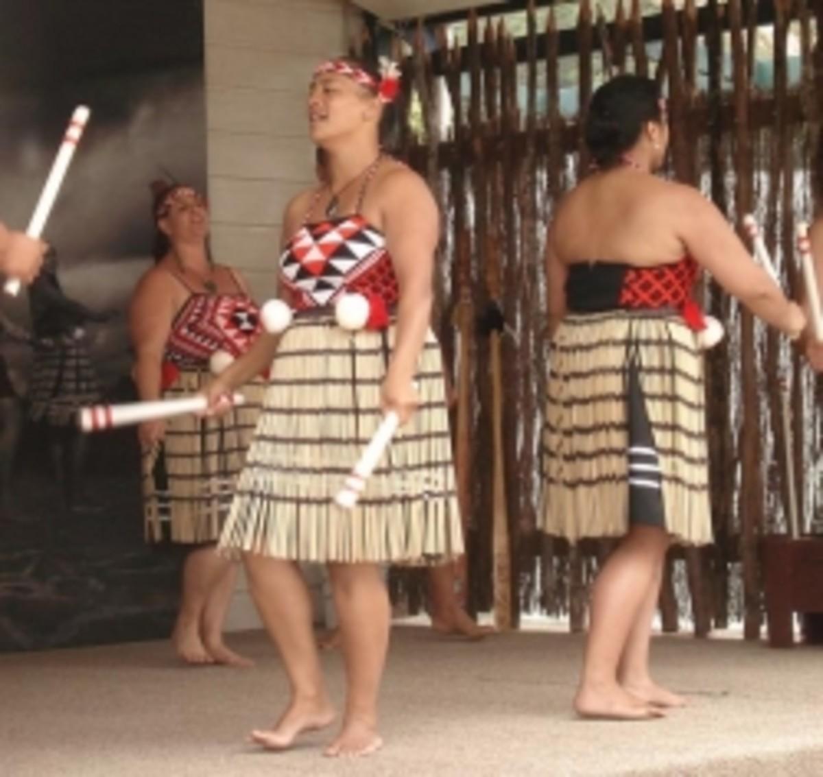 A Maori woman with long sticks.