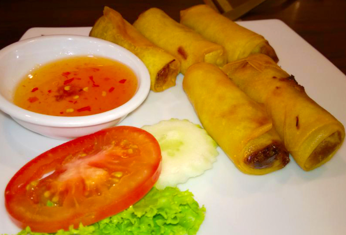 Deep-fried popiah is a crunchy and delicious snack. Chili sauce and garnish with tomato-cucumber and lettuce.
