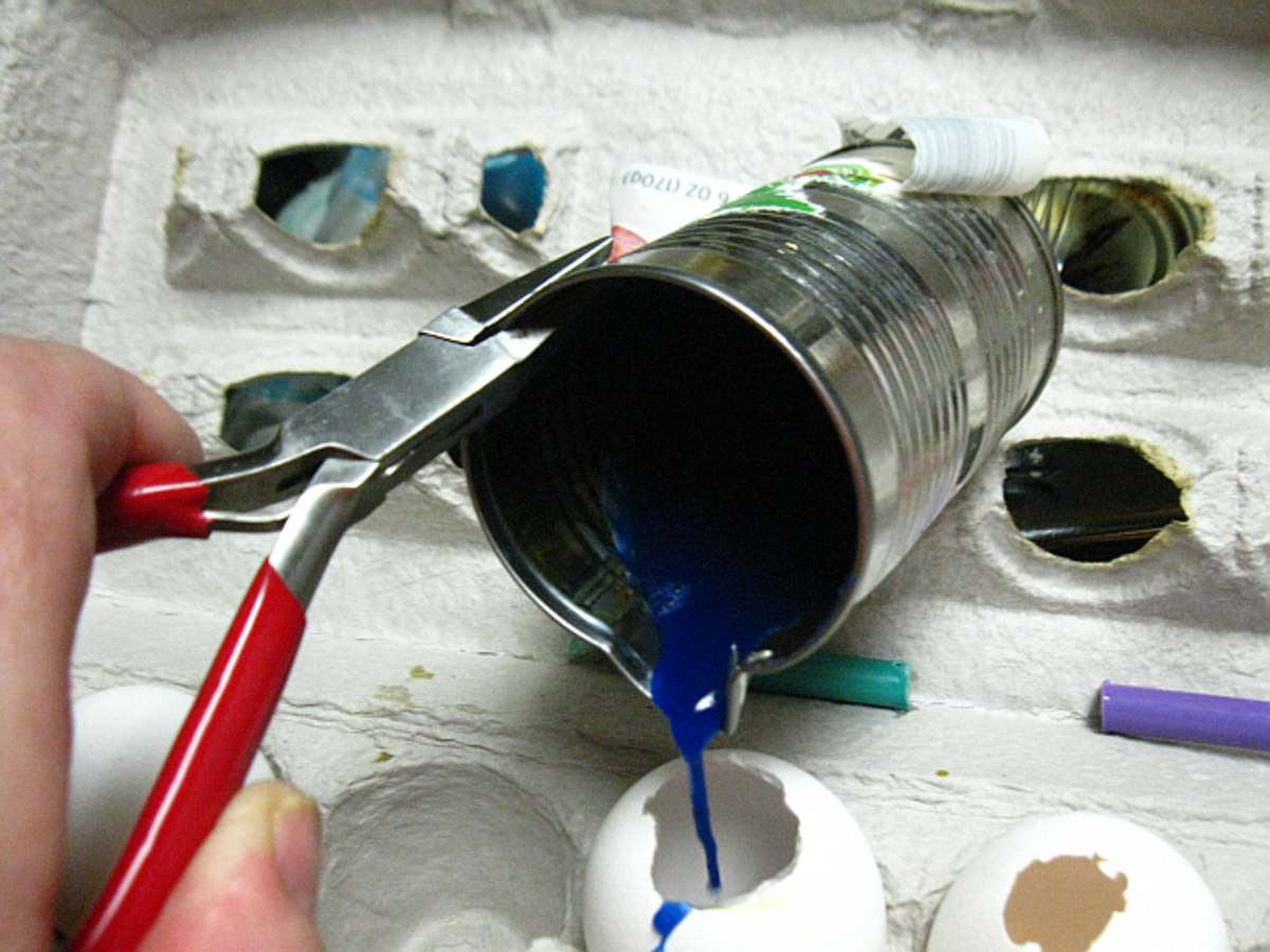 using the pliers to hold the tin can, slowly pour cooler melted wax into egg shell