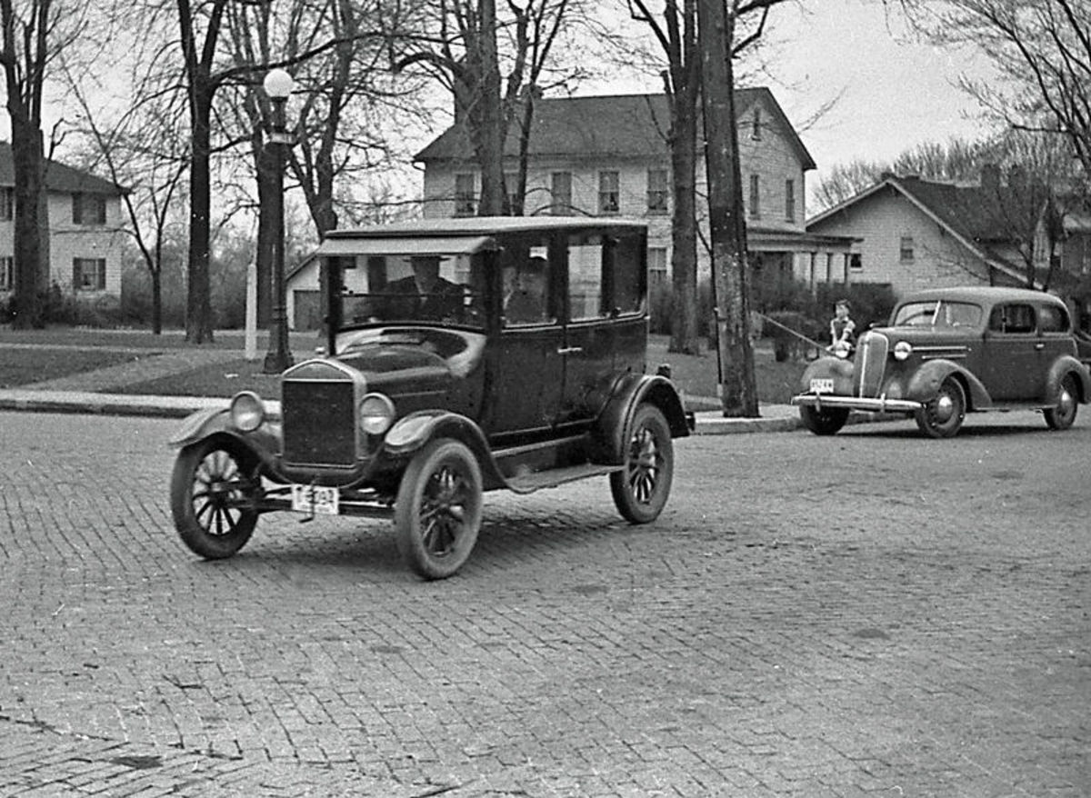 Early 1920s Model T Ford at center with 1936 Chevrolet at right.