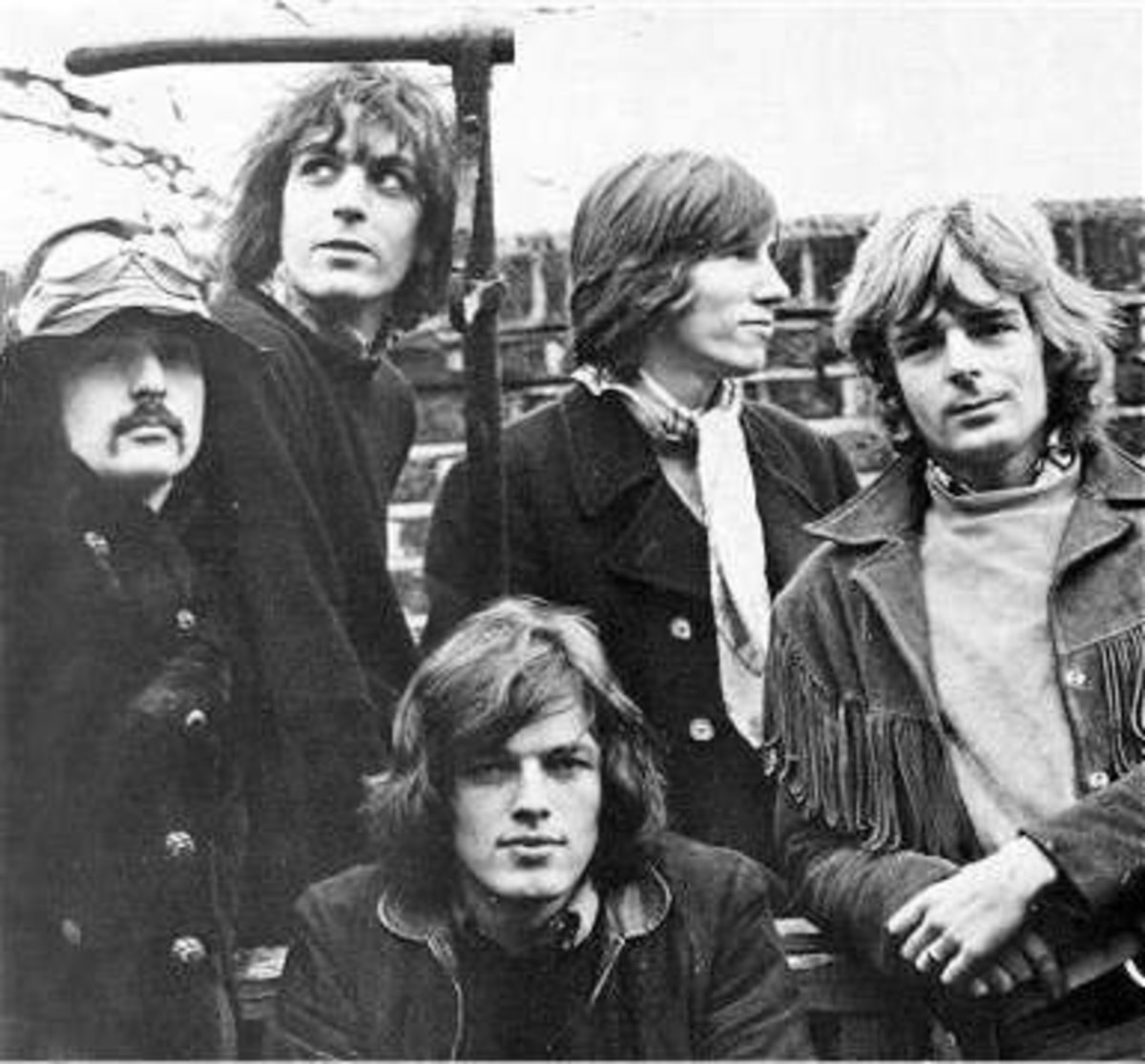 Photograph of all significant members of Pink Floyd. Nick Mason, Syd Barrett, Roger Waters, Richard Wright, and David Gilmour (seated)