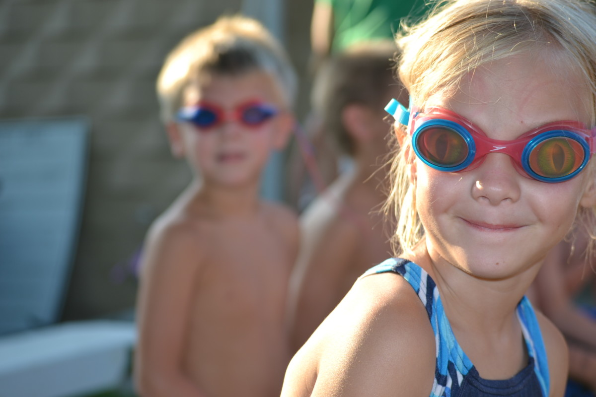 Daughter in the bullpen waiting for race. Her twin is waiting behind her for the next swim race.