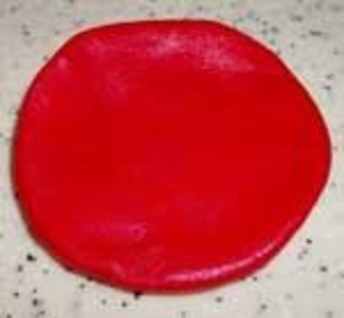 Roll out a ball of red fondant slightly larger than the ball of off-white fondant for the gills and flatten it down into a round.