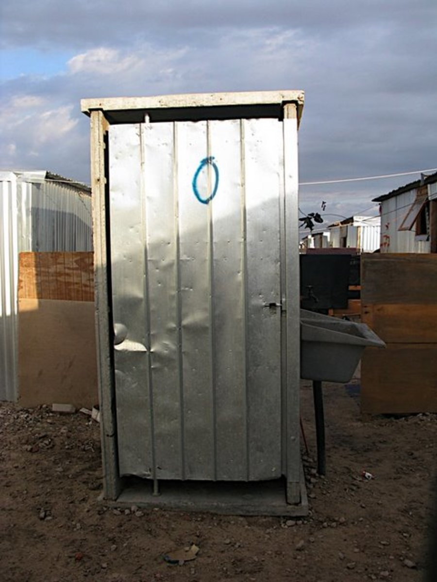 An outside toilet(hole dug in the ground and covered with zincs