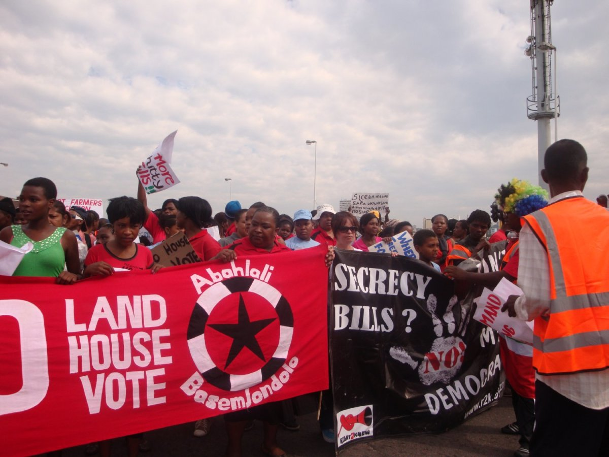 """No Land! No House! No Vote"""" The Banners of the Abahlali baseMjondolo blazon on red and Black and white print as they march to make their case"""