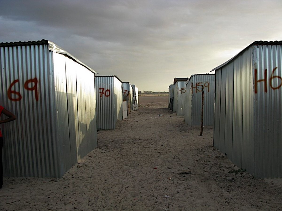 The lining up of and making of the tin shacks row of corrugated structures which were mostly one room(so to speak) and were finally enclosed in barbed wire forming the Blikkiesdorp Tin Shack Town