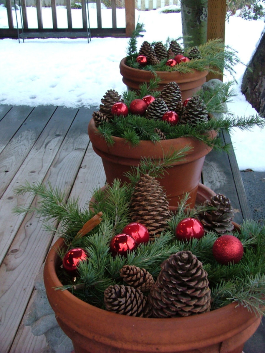 large clay pots with pine cones, greenery and ornaments- gorgeous!