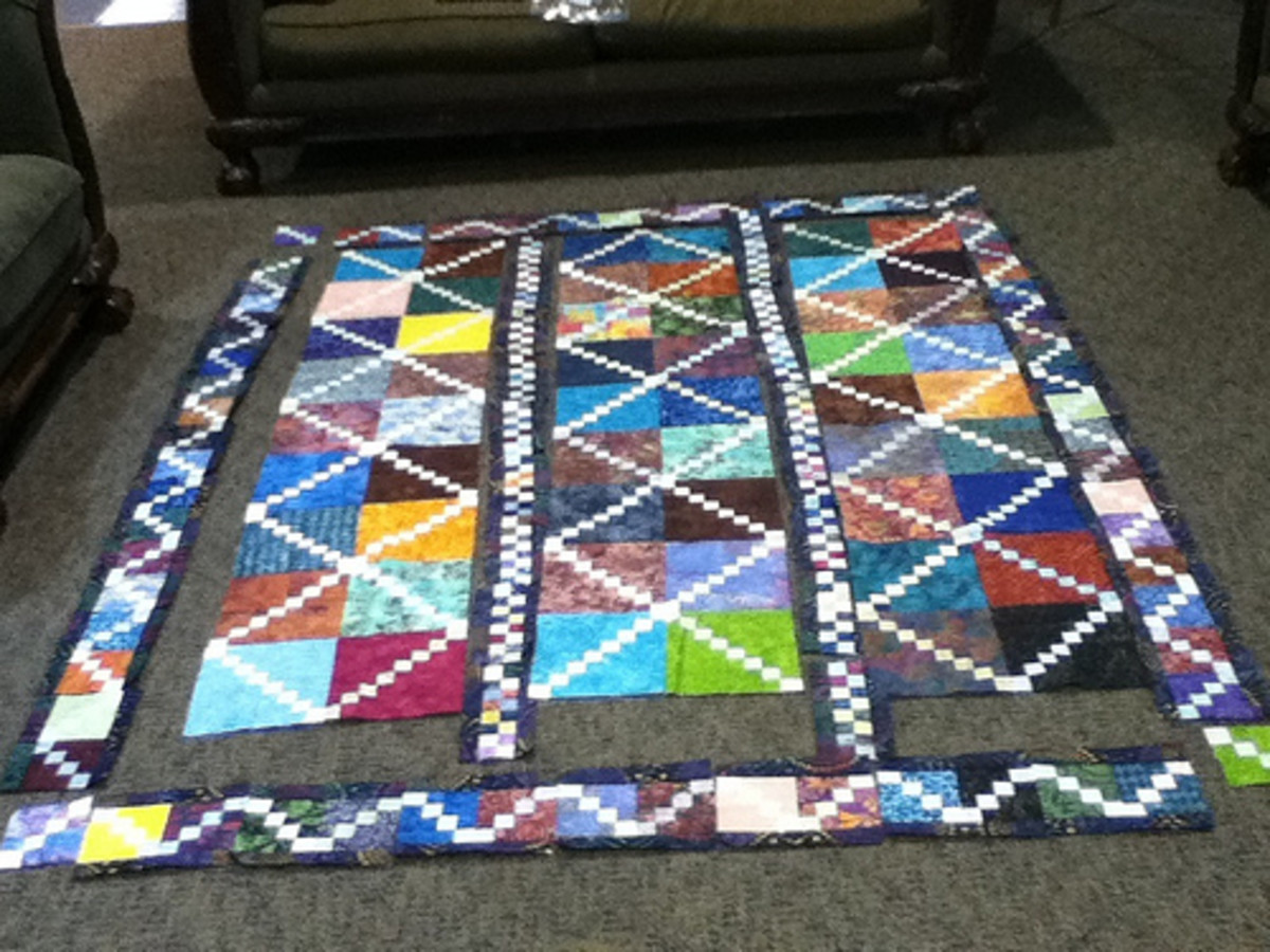 This unfinished quilt uses a combination of batik fabrics with a solid white fabric.
