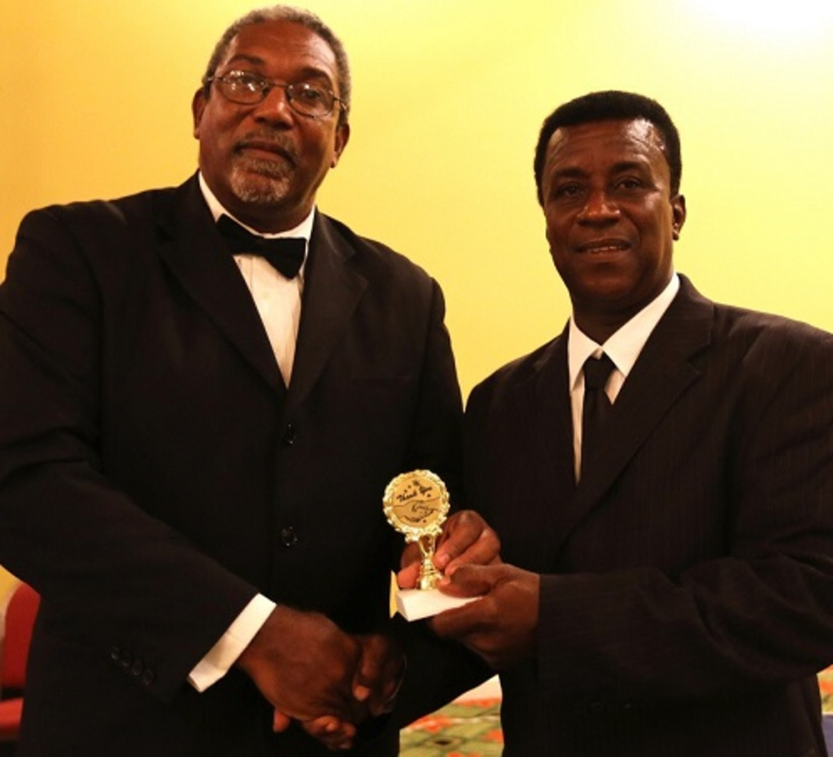 Former Leeward Islands Cricket Association (LICA) President and West Indies Cricket Board (WICB) Director Mr. Gregory Shillingford presents an award to Willett in June, 2014.  Willett is on the right.  – (WICB Media photo)