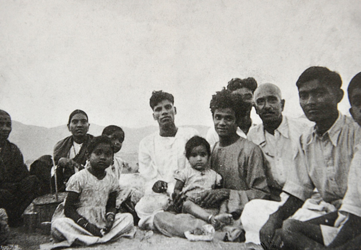 Swami seated with a group of devotees from Bangalore on the sands of River Chitravati.