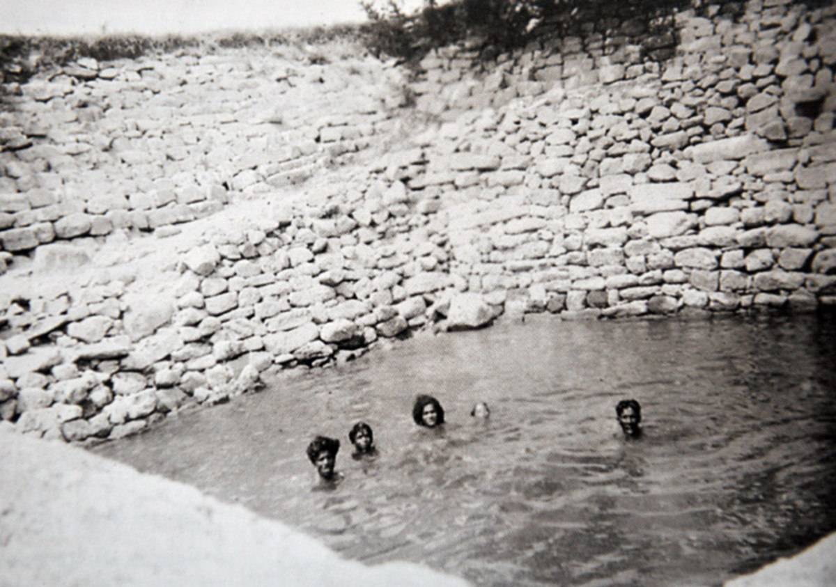 Swami enjoying a swim with some of the male devotees in the village well.