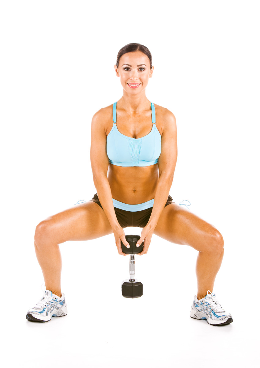 woman exercising with barbell with the wide squat working the interior of the thigh