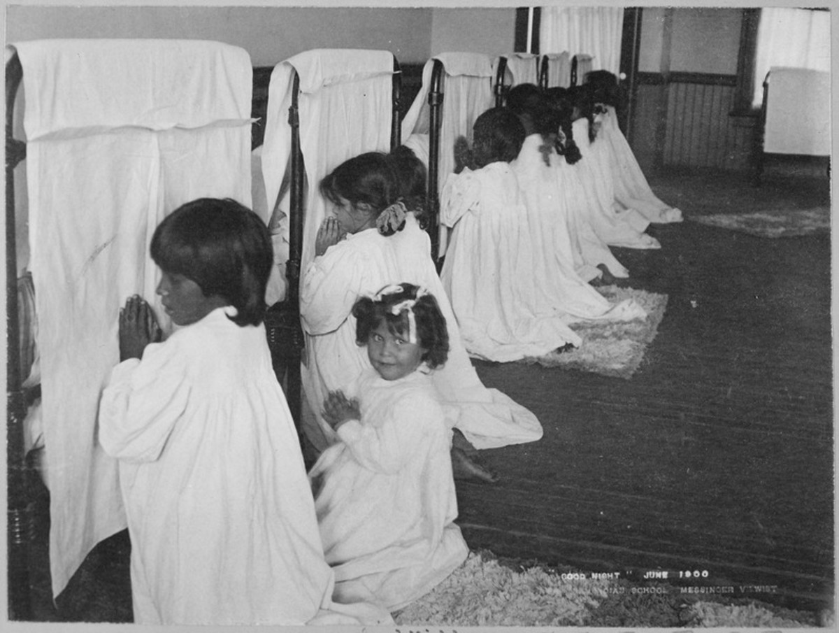 Little girls praying beside their beds at the Phoenix Indian School circa 1896-1900.
