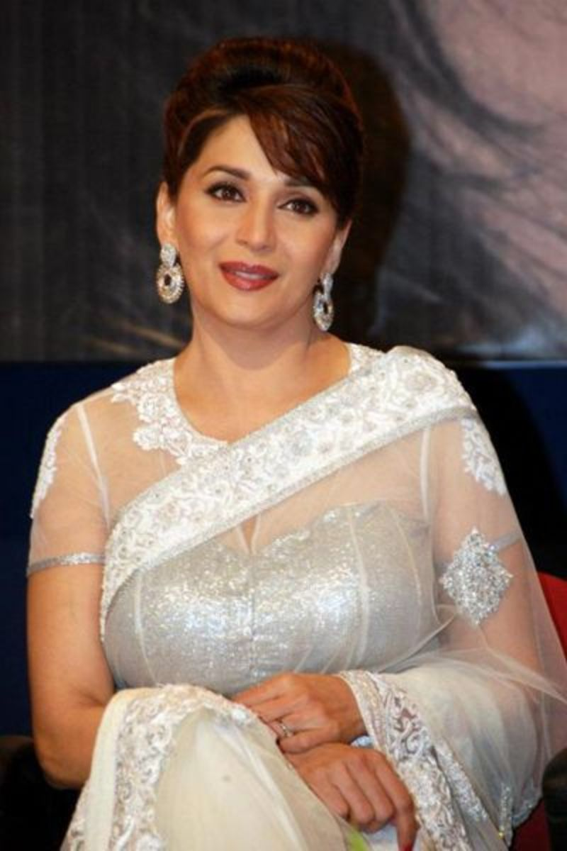 Madhuri is famous white and silver saree blouse with half body transparent and half body covered.