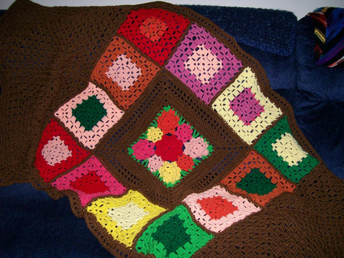Finished creative afghan using leftover center square and other yarns from original project.