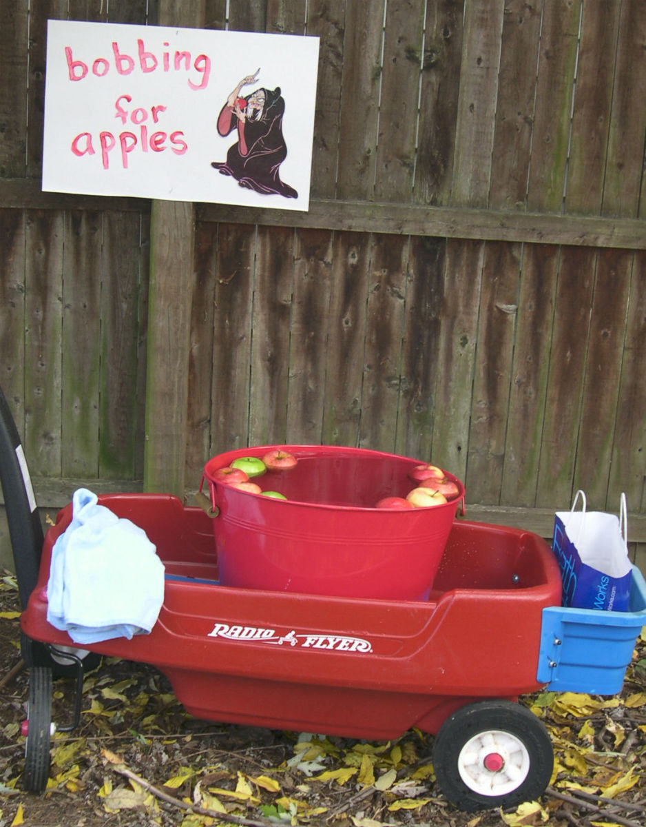 Place the tub for the apple bobbing game in a wagon so it is the right height for little ones. Also provide a towel or two so kids can dry their faces.
