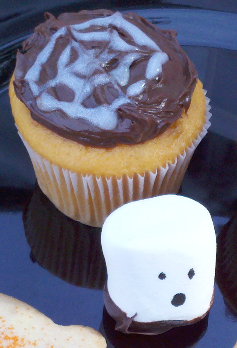 Spider web cupcakes and ghost marshmallows are easy to make treats for a Halloween party.