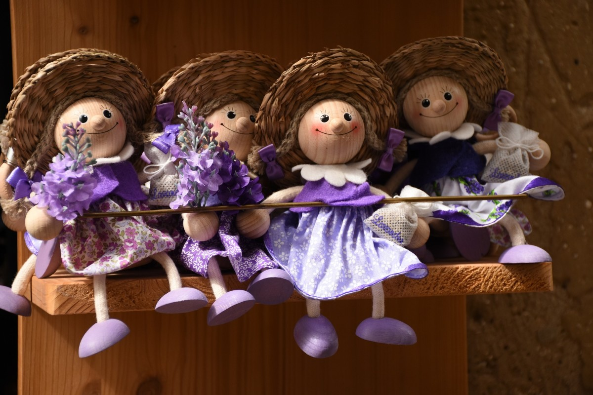 Wooden dolls displayed on shelving.