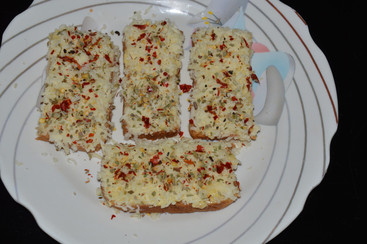 Step two: Spread grated cheese on top of the buttered layer. Sprinkle the mixture of seasonings on the top of each slice.
