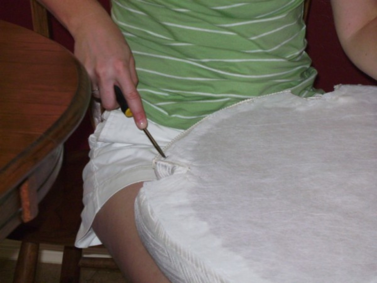If you remove the existing fabric, use a flat head screw driver to pry the staples out of the wood seat bottom.  You may need to pull the staples out with pliers after you loosen them with the screwdriver.