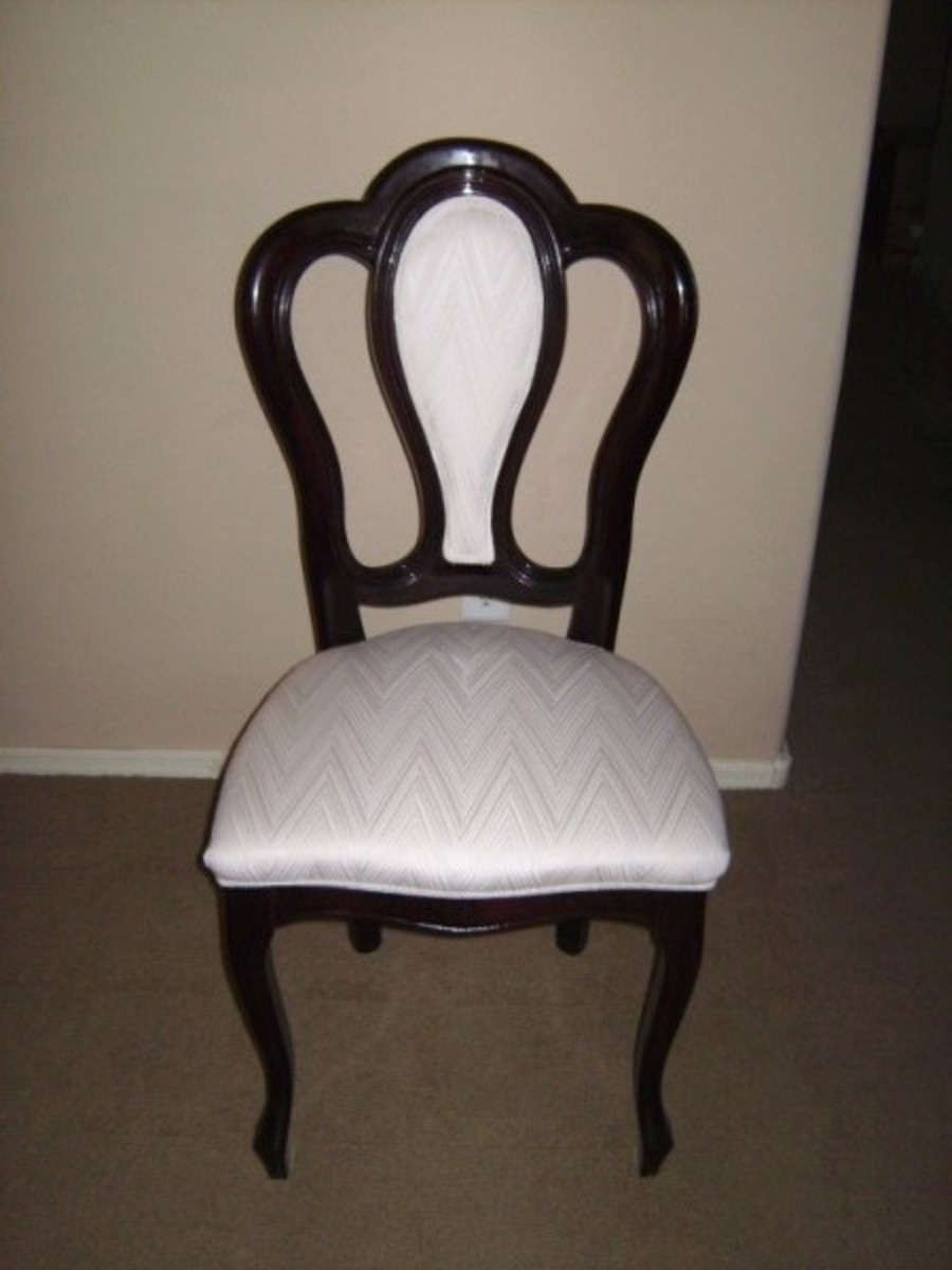 The chair originally had a dark cherry colored shiny finish with white upholstery on the seat and the back