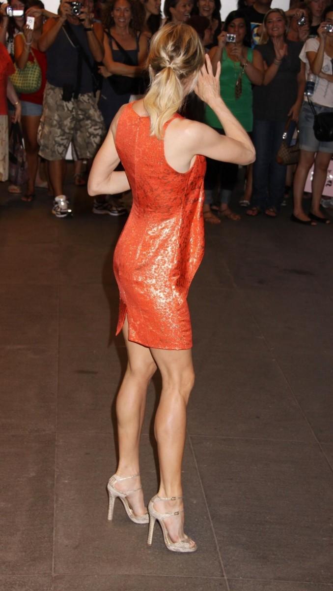 Renee Zellweger show off her sexy legs in a short orange dress and towering high heels