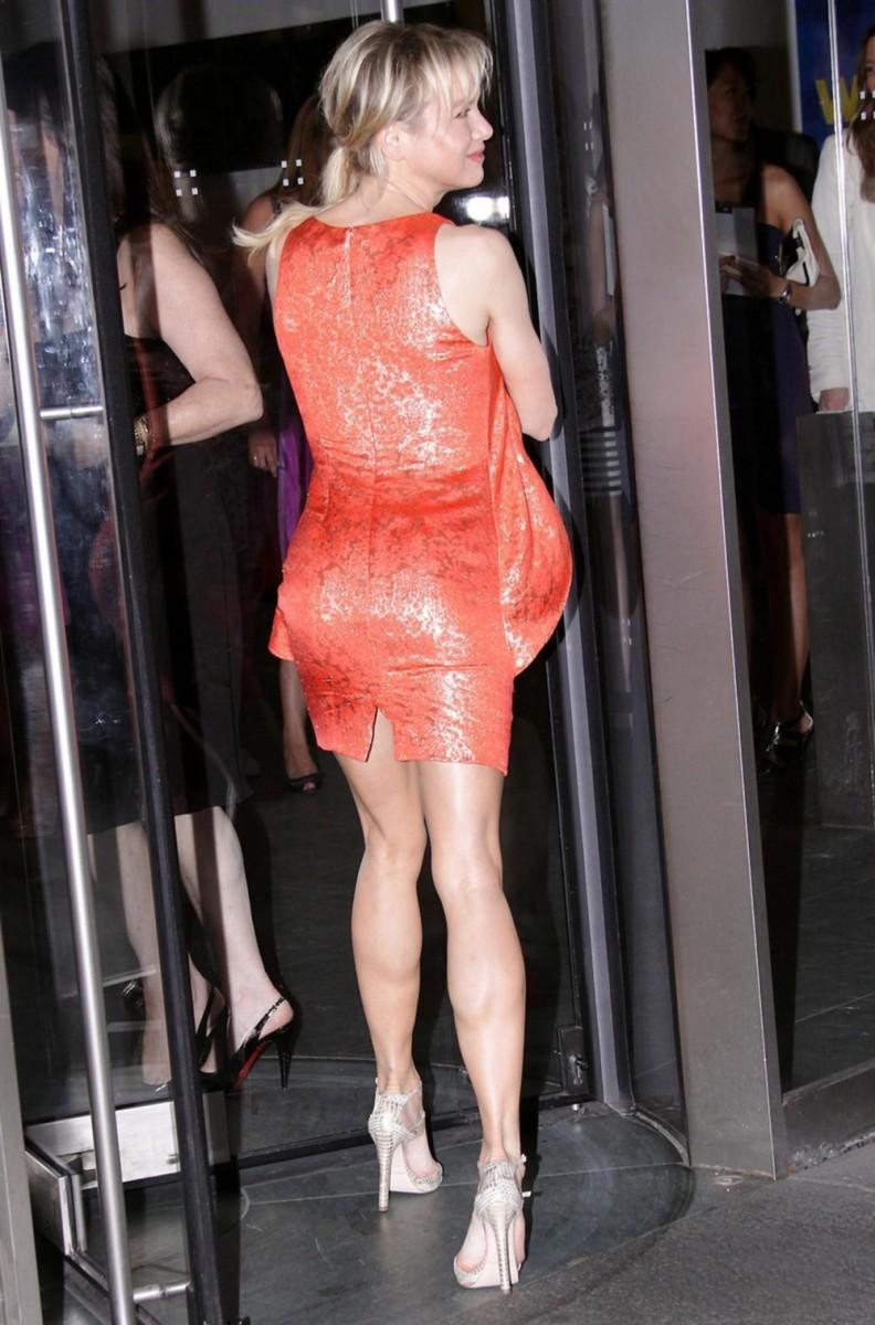 Leggy Renee Zellweger in a short orange dress and sky high heels