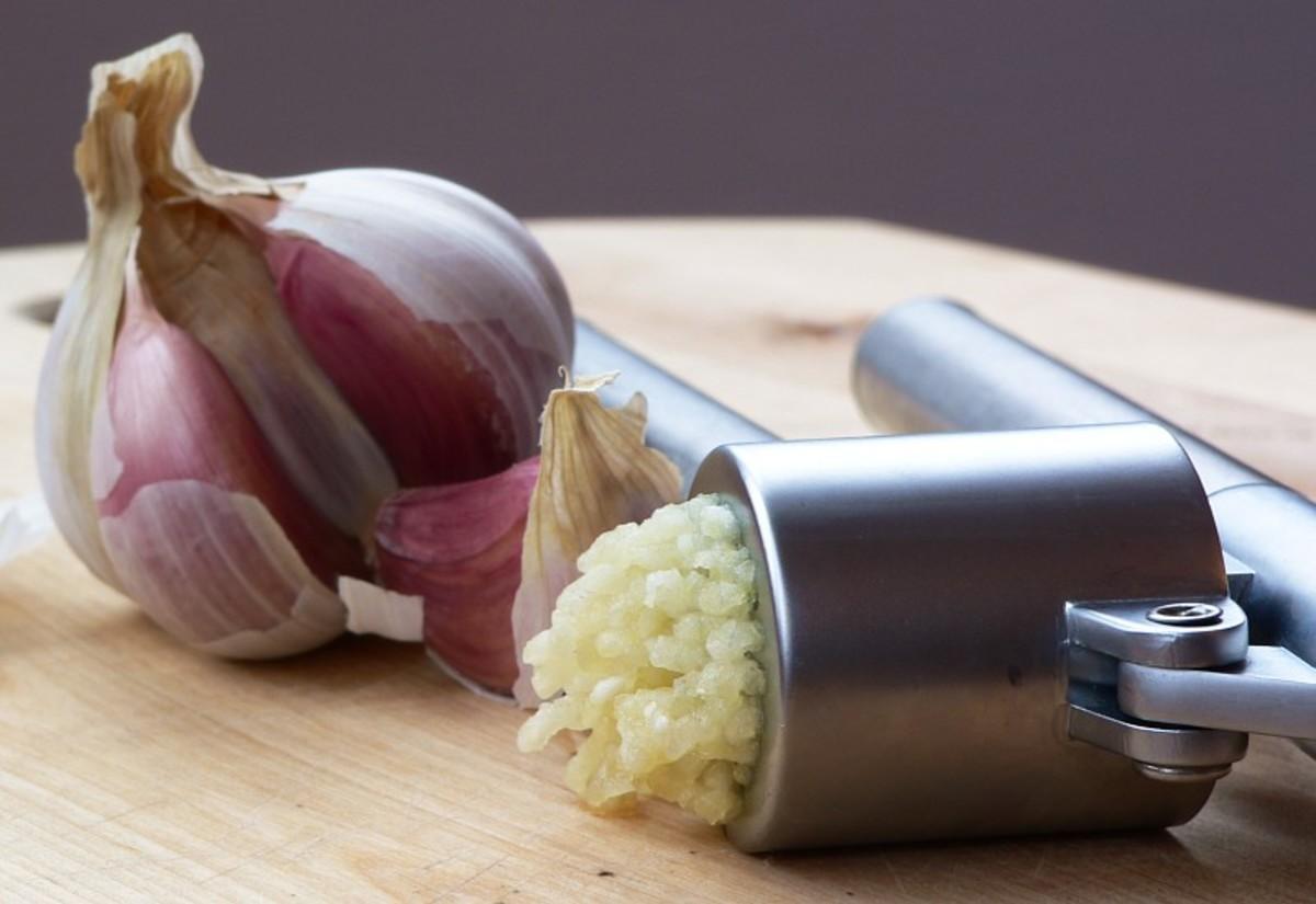 Garlic that is being crushed using a garlic press