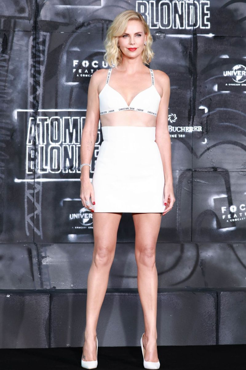 Charlize Theron in a two piece bralet and high waisted short skirt and white pumps promoting her latest movie premiere