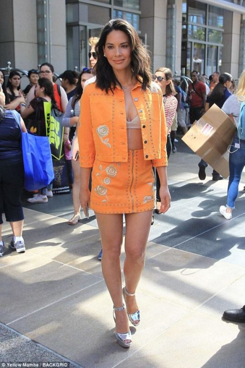 Olivia Munn in an open orange mini jacket revealing a bra with matching short skirt and silver high heel platform sandals