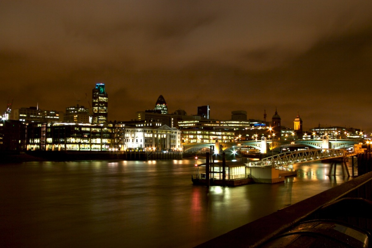 A picture of teh River Thames at night as it flows through the English capital, London.  The River Thames is the longest river completely in England.
