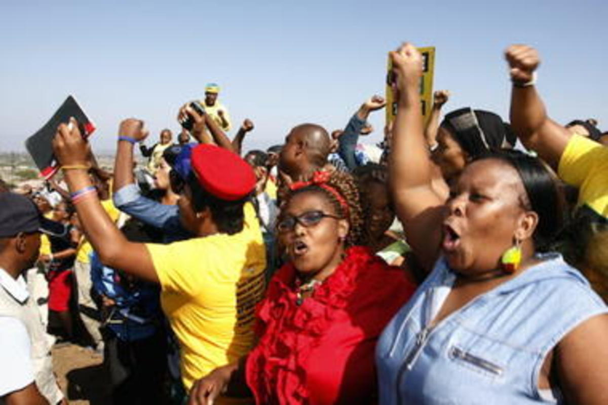 Women wave as South African president and leader of the African National Congress (ANC), Jacob Zuma, arrives to cast his vote in Ntolwane, rural KwaZulu Natal province, South Africa, Wednesday May, 7, 2014. The country goes to the polls in the fifth