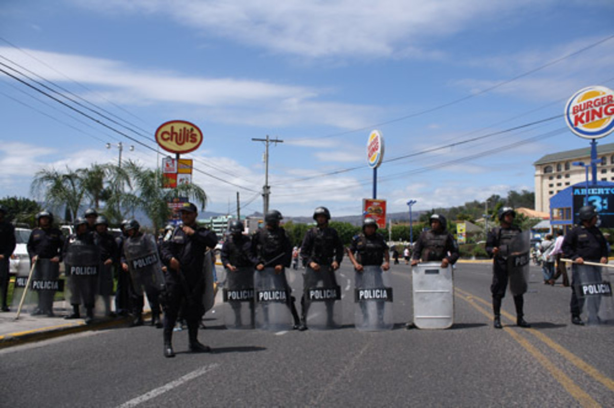 Honduran police officers barricade the street to block of a peaceful, pro-democracy protest march in the capital of Tegucigalpa on February 2010