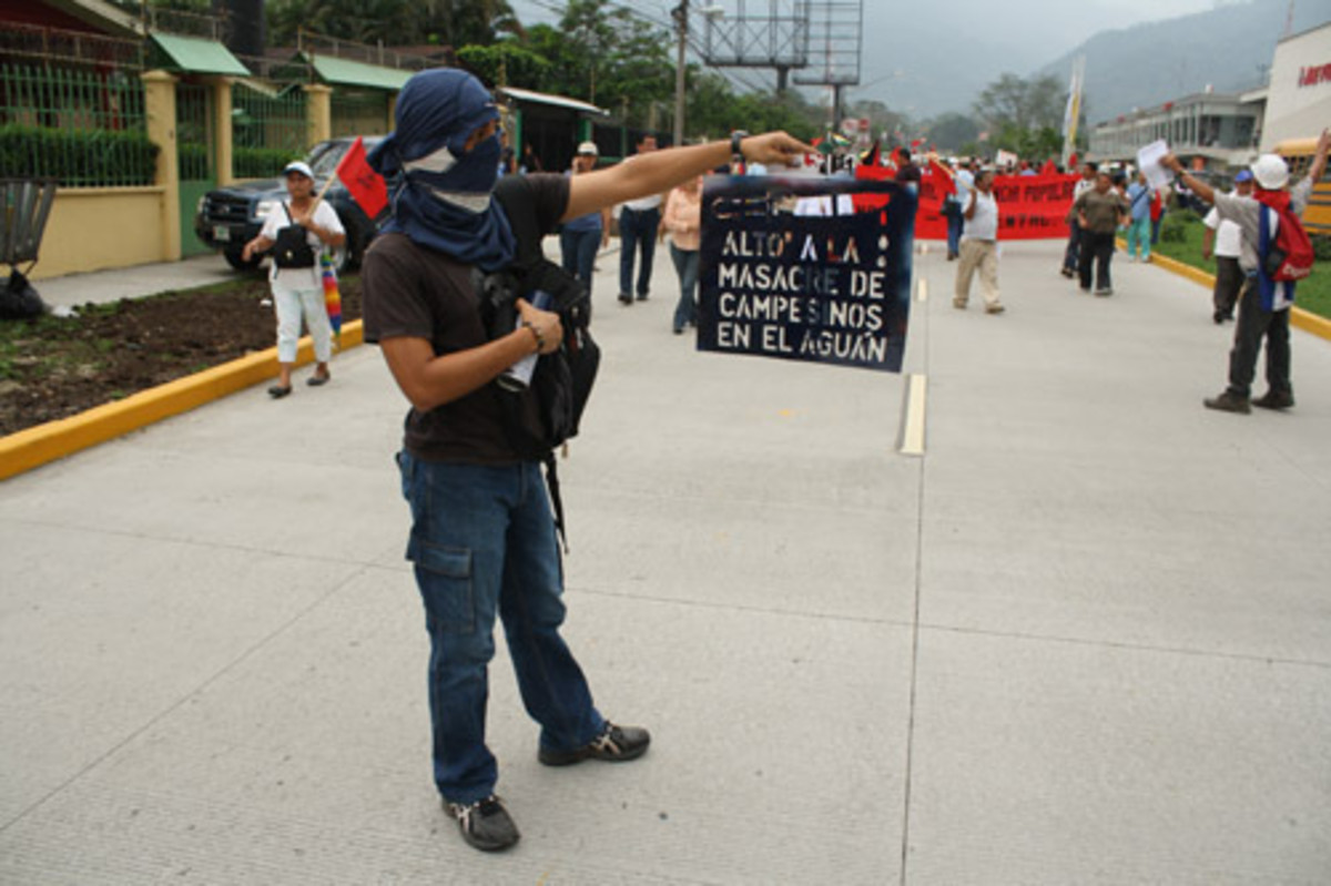 "During a march of February 2010 in San Pedro Sula, a youth who was pro-democracy holds a sign which read: ""Stop the massacre of the peasants in Aguan"