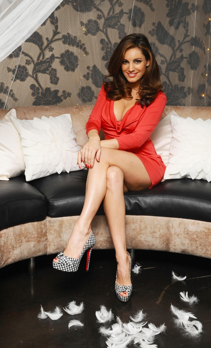 Kelly Brook crossed legs in a hard working red dress and sky high Christian Louboutin high heels