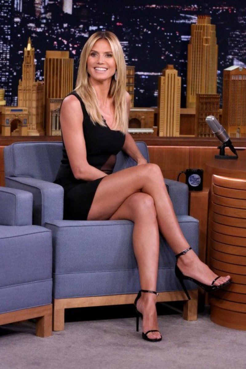 Heidi Klum gorgeous crossed legs in a little black mini dress and ankle strap high heels sandals